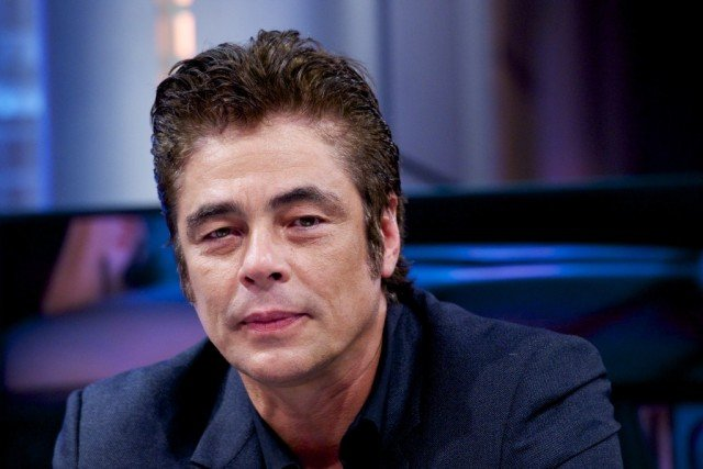 Benicio Del Toro sitting down in a blue suit and starting straight ahead.