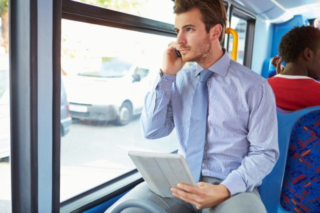 Man on the phone traveling by bus