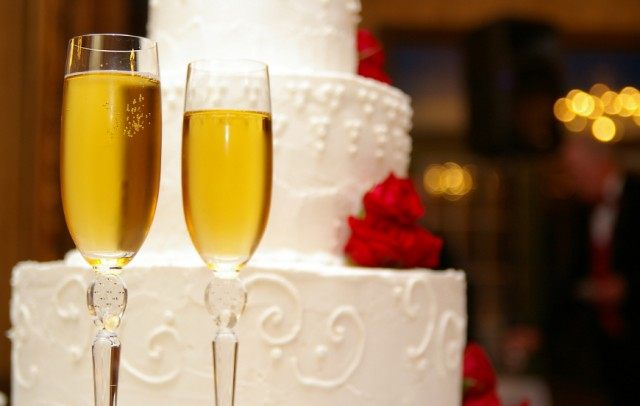 Wedding cake seen behind two glasses of champagne.