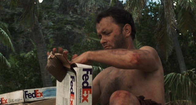 A shirtless, dirty, Tom Hanks opens a Fed Ex box, while sitting on the ground
