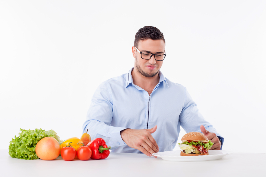 A man reaching for a burger instead of veggies