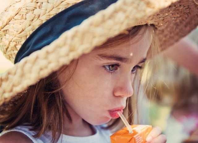 child drinking from a juice box