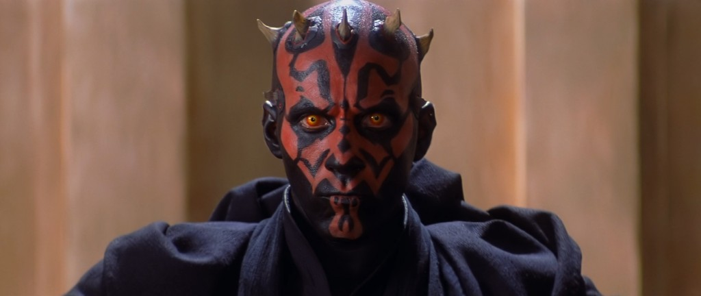 Darth Maul, wearing black robes, and looking intensely into the camera