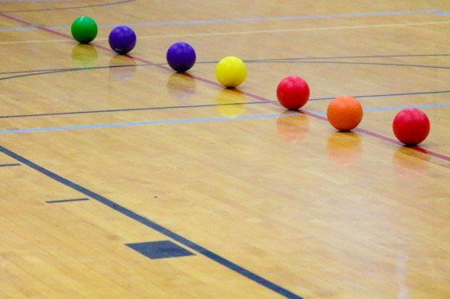 dodgeballs lined up in a gym