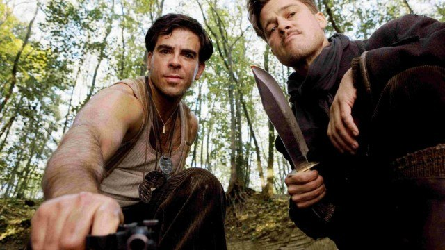 Eli Roth and Brad Pitt holding knives to the ground in Inglourious Basterds