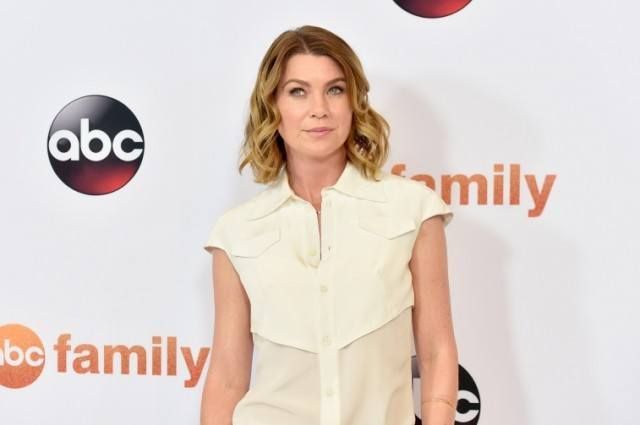 Ellen Pompeo posing for photographers on a red carpet.