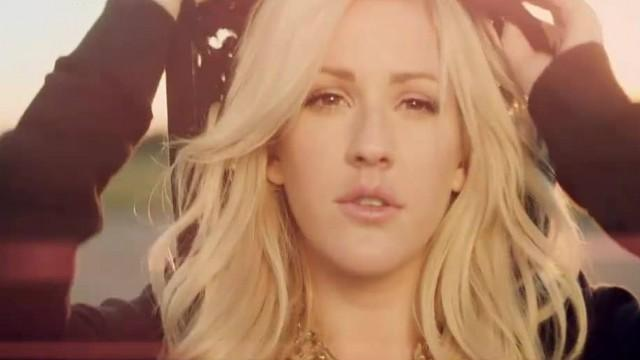 Ellie Goulding is pulling up the hood of her black sweater.