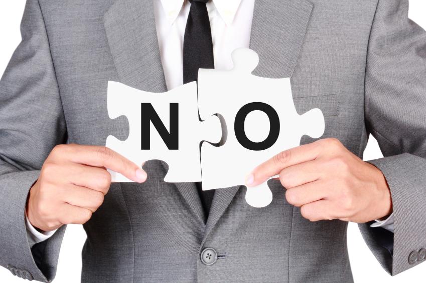 "A businessman holding up a ""no"" sign"