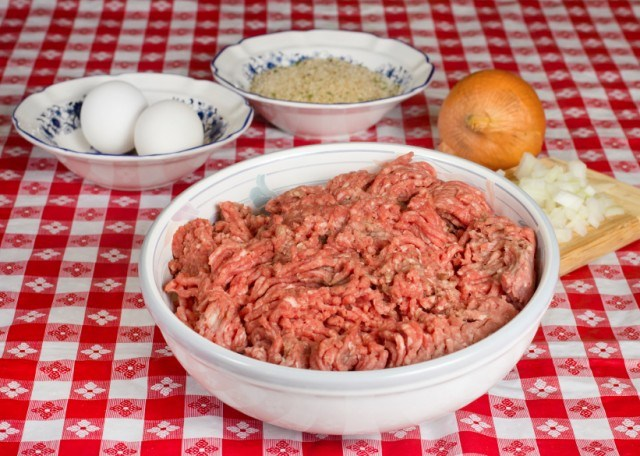 ground beef in a bowl next to other ingredients