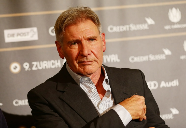 Harrison Ford is wearing an unbottoned shirt and a suit jacket.