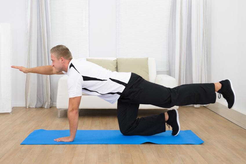 Man doing bird dog exercise on a mat