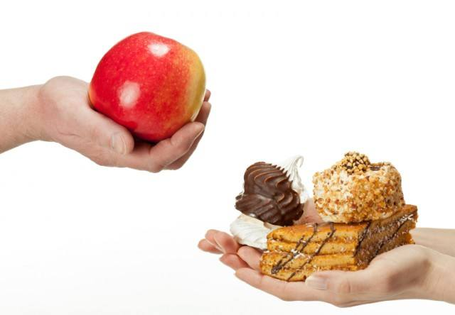 Two hands holding a red apple and sweet deserts.