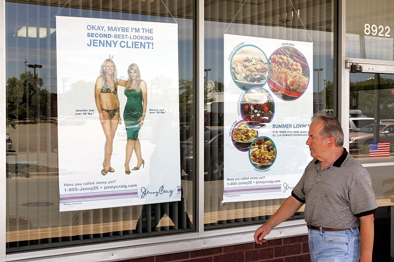 man walking by a storefront with diet advertisements