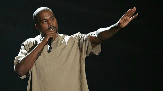 Kanye West is talking on stage with one arm out.