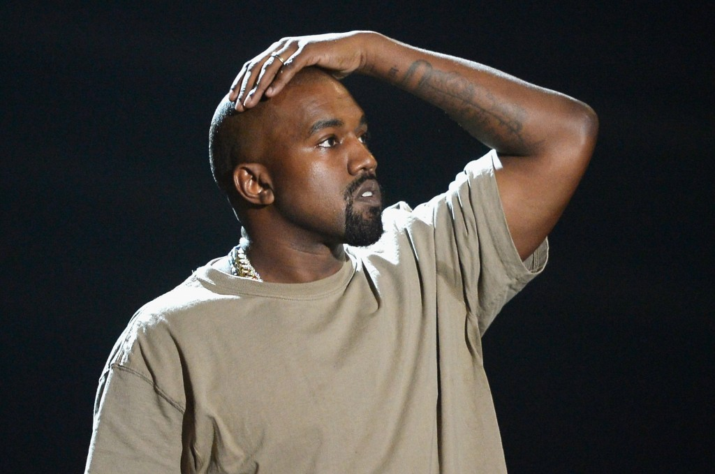 Kanye West in a tan shirt with his hand on his head looking on