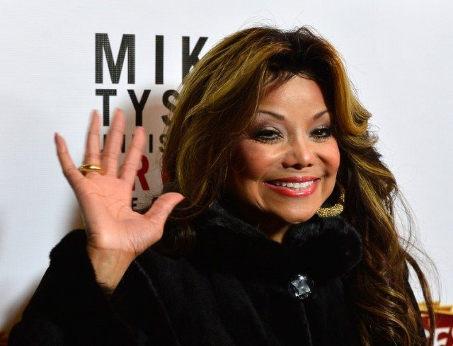 La Toya Jackson waving and smiling while on a red carpet.