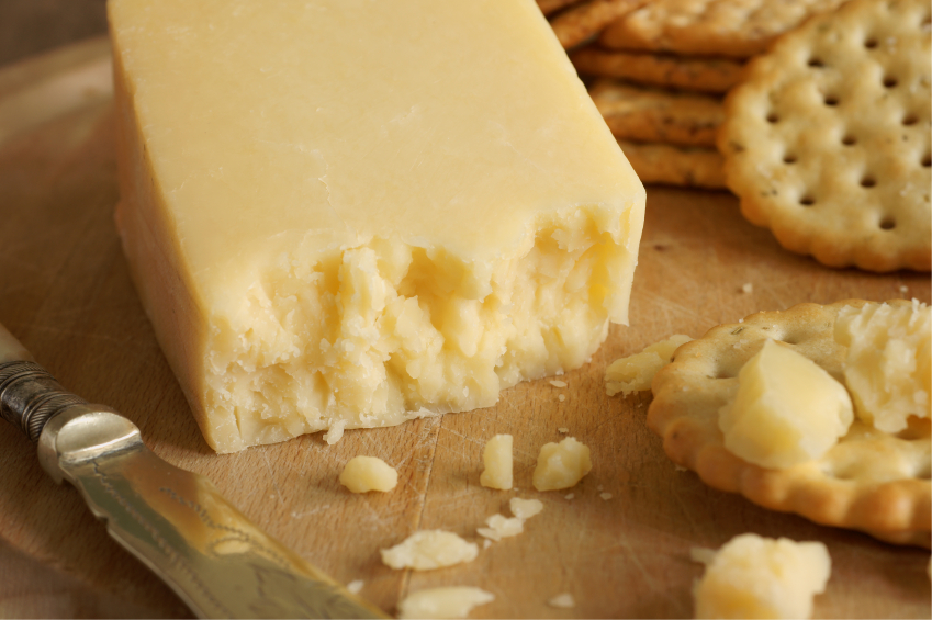 Block of cheese with crackers on cutting board