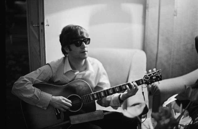 John Lennon playing on an acoustic guitar while sitting on an archair.