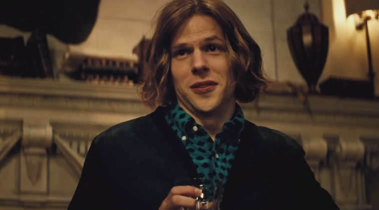 Lex Luhtor, holding a glass in his hand and wearing a collared blue shirt with black polka dots