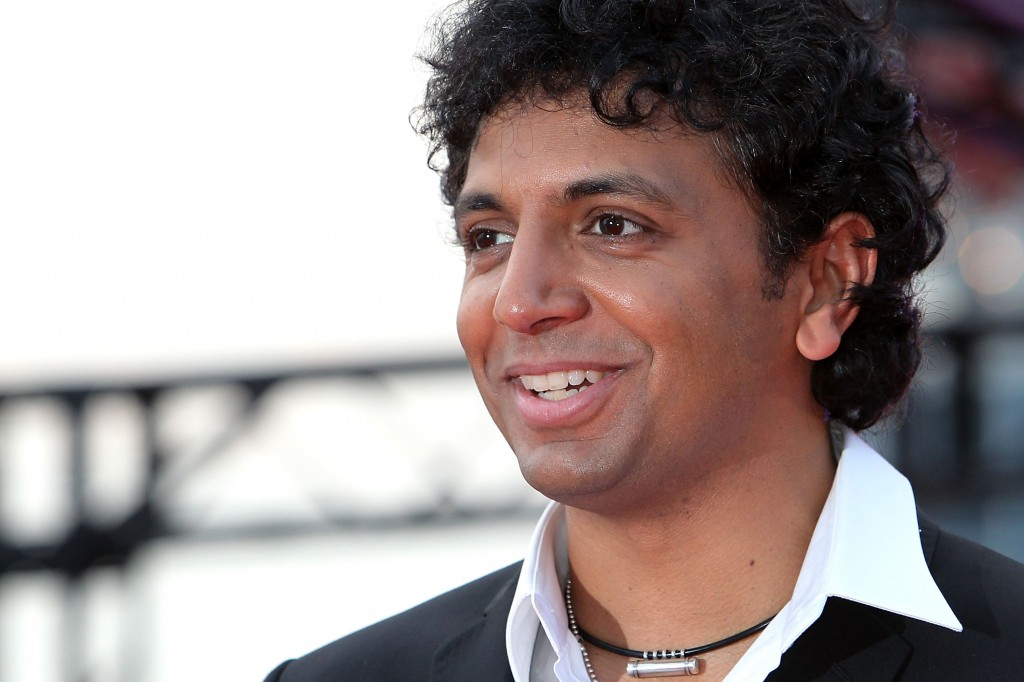 M. Night Shyamalan is smiling on the red carpet.