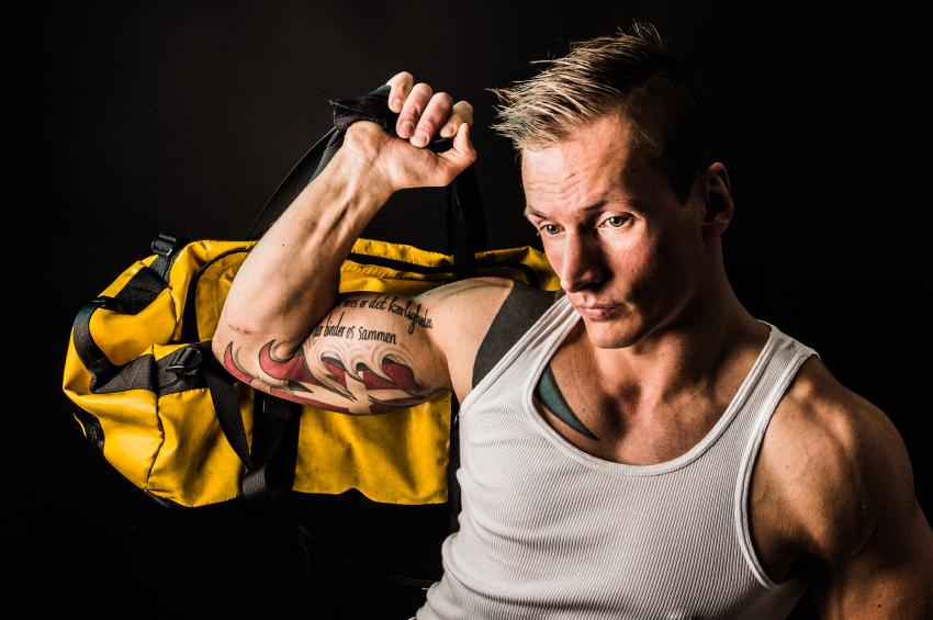 muscular man holding his gym bag