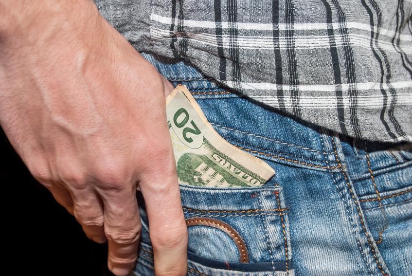 man putting cash in pocket