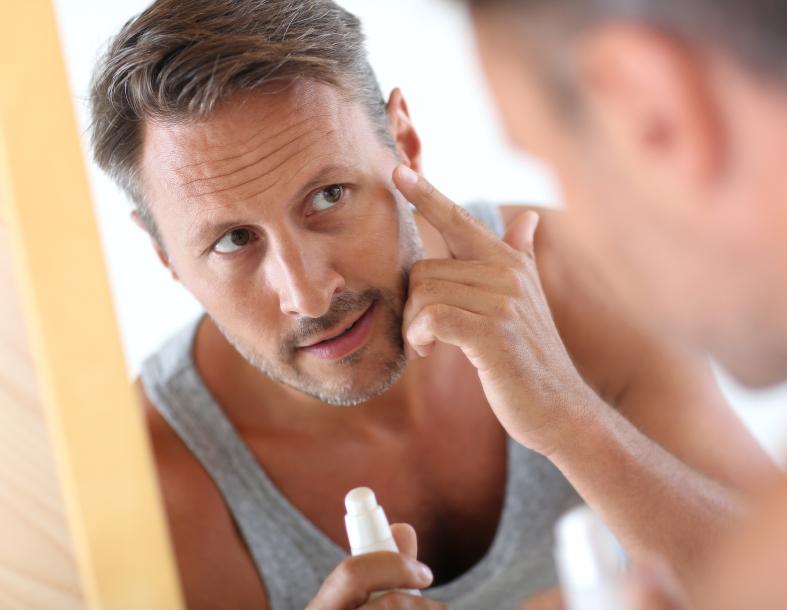 Man in bathroom applying cosmetics on his face