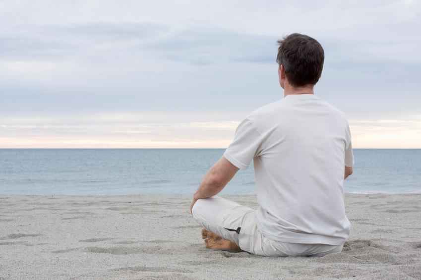 man meditating on beach