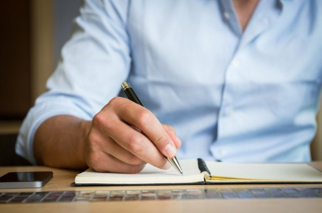 A man writes in a notebook with a pen.