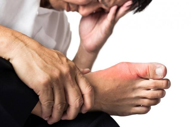 A man massages his inflamed foot.