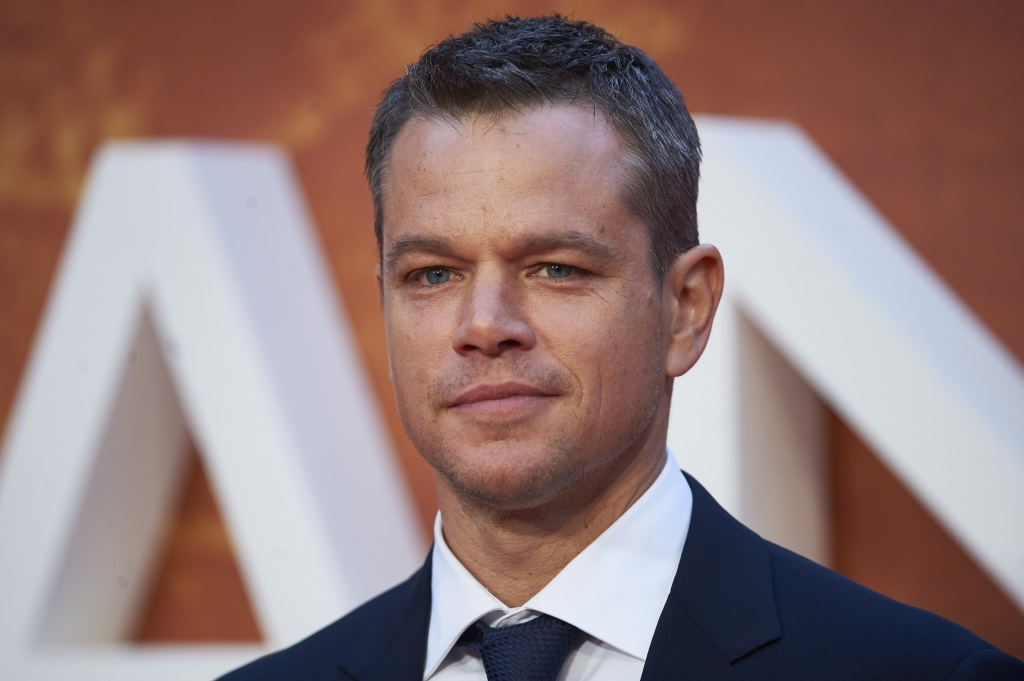 Matt Damon looks ahead and stands in a blue suit at an event