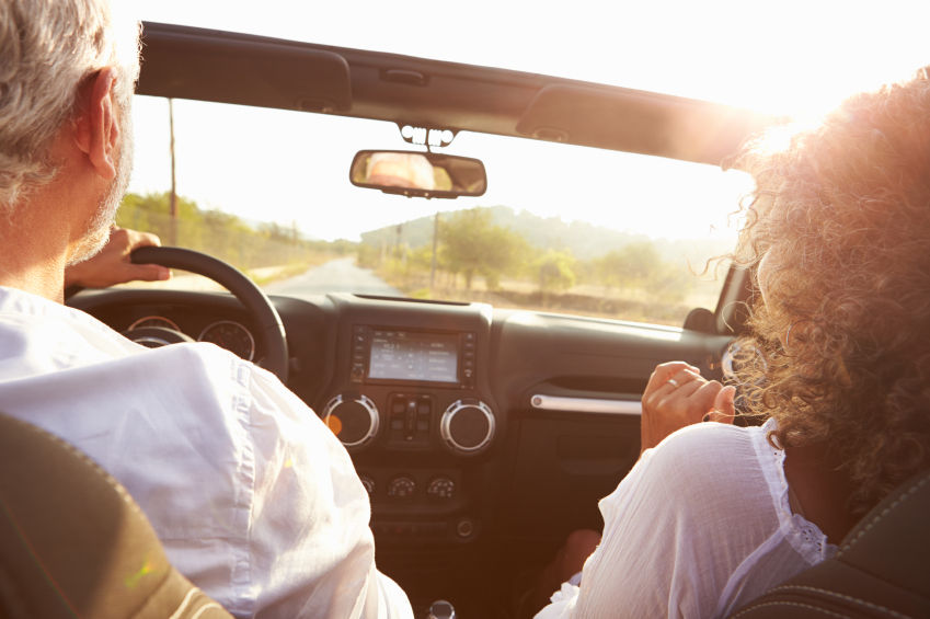 An older couple driving at sunset