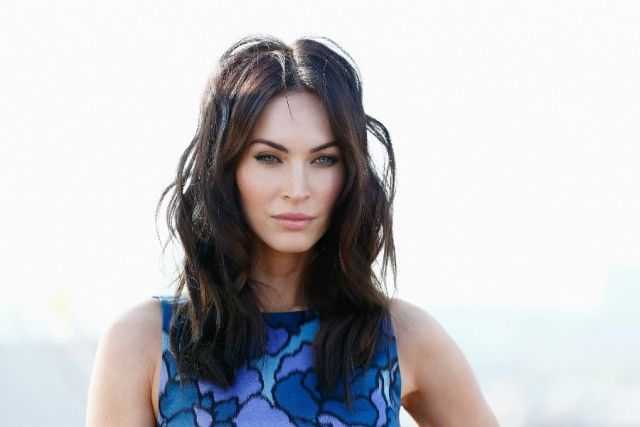 Megan Fox posing in a blue floral dress against a white background.