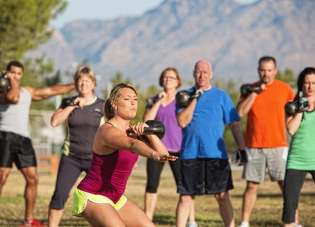 Woman working out with kettlebell instructing a class.