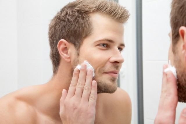 Man moisturizing in the mirror