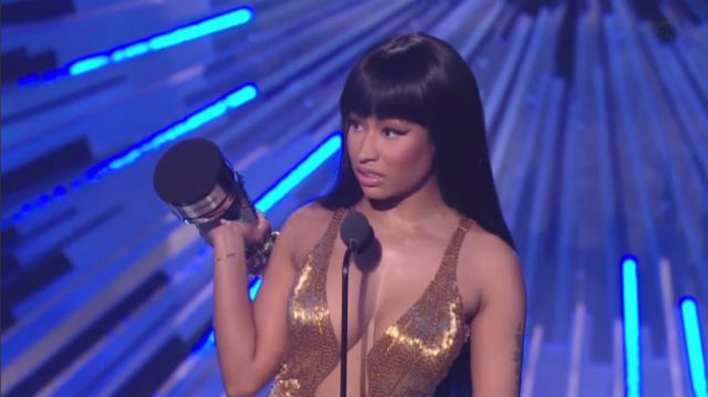 Nicki Minaj looks disgusted as she's on stage and holding her award.