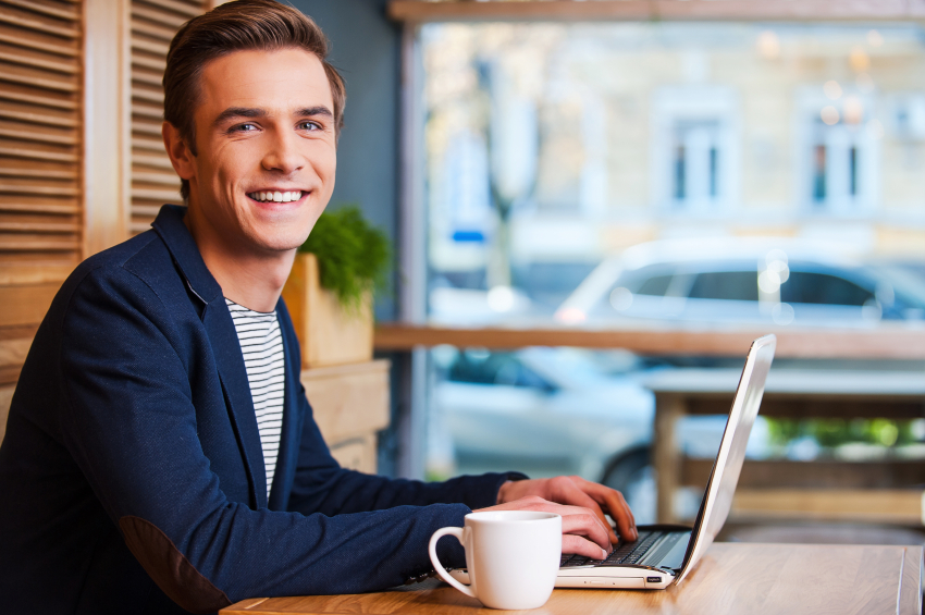 Smiling man typing on laptop