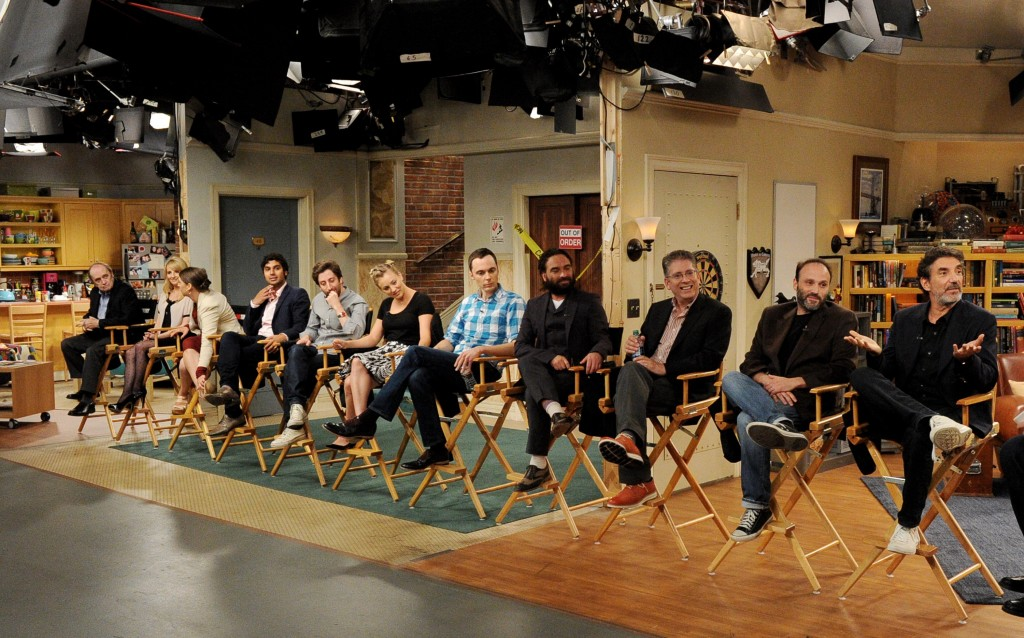 The cast and crew of the Big Bang Theory sit in chairs on set