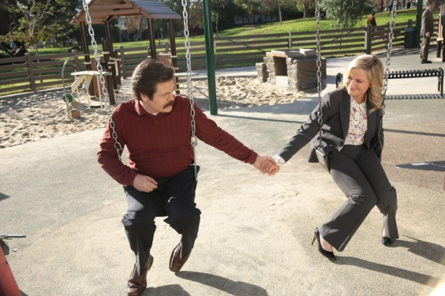 Ron and Leslie hold hands while sitting on swings at a playground.