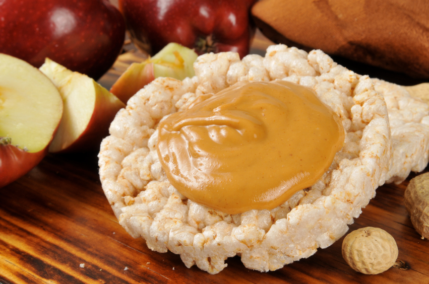 A rice cake with a serving of peanut butter