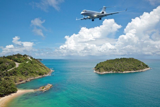 Private jet flying over tropical islands