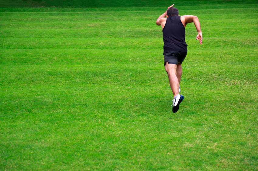 man sprinting up a grass-covered hill
