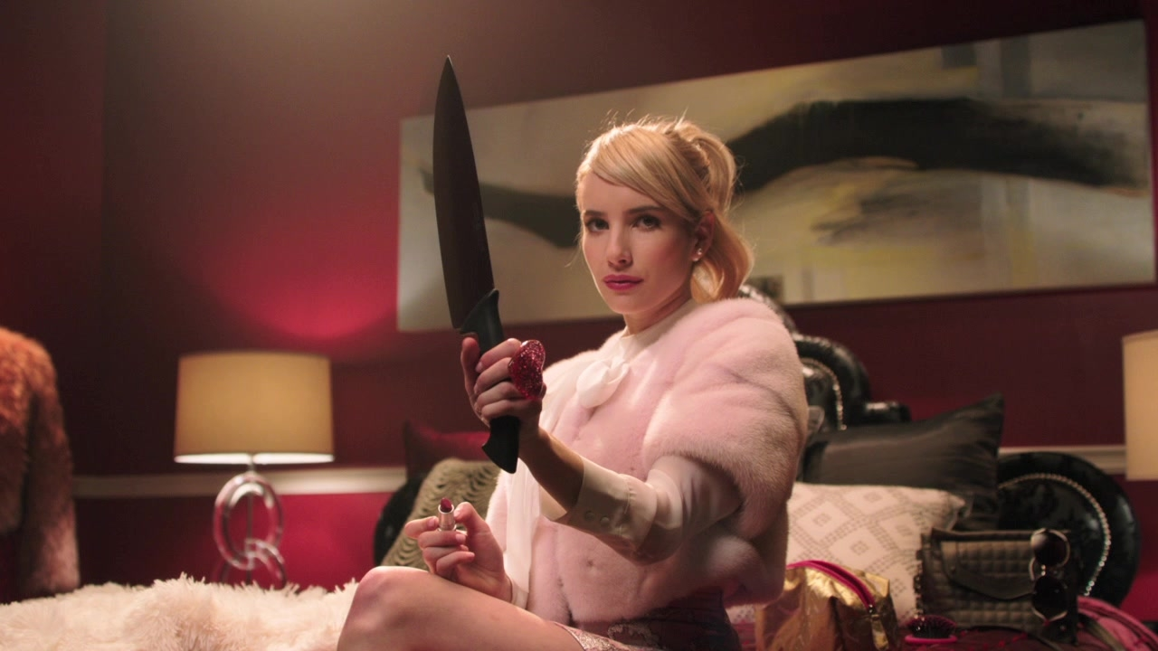 A blonde girl in a pink coat holds up a knife