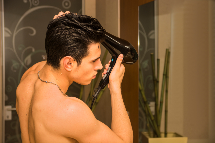 blow drying his hair in the bathroom