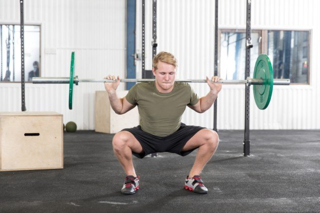 man doing barbell squats at the gym