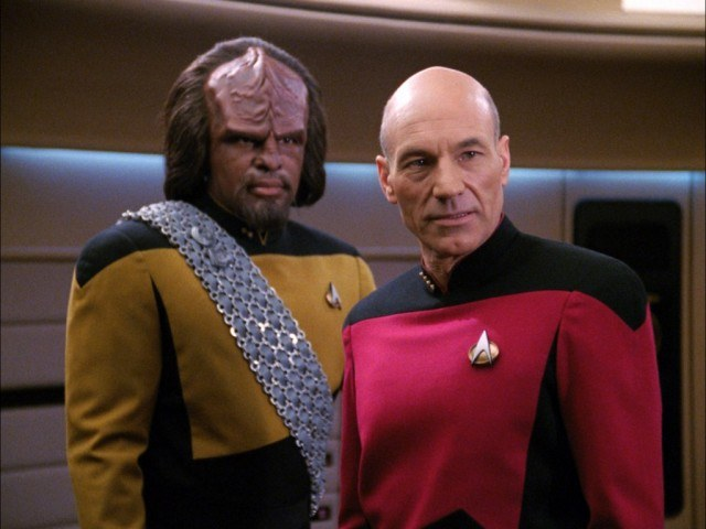 Captain Jean-Luc Picard stands next to Captain Worf Michael Dorn stand next to each other.