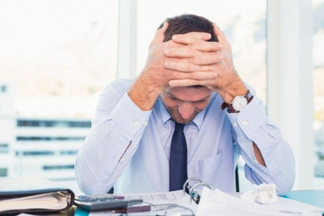 Stressed businessman with head in hands