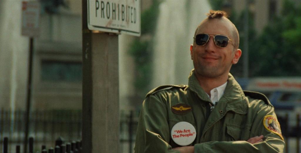 Robert De Niro smiles, wearing sunglasses and sporting a mohawk