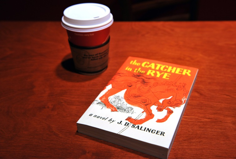 The Catcher in the Rye sitting next to a coffee cup on a red table