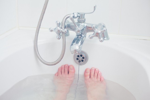woman with feet up in the bath tub